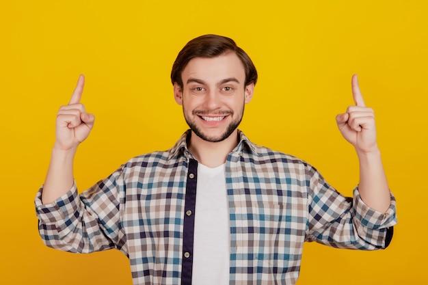 若い魅力的な男の幸せなポジティブな笑顔のポイントの指の空のスペースの選択の写真は、黄色の背景に分離された販売を提案します