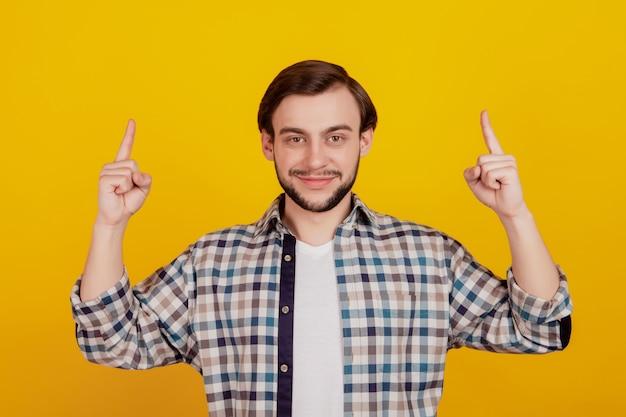 若い魅力的な男の幸せな笑顔ポイント指空のスペースプロモーション広告の選択の黄色の背景に分離された写真