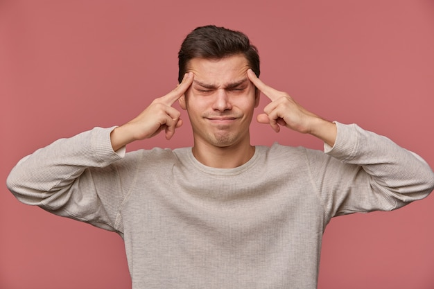 Фотография молодого привлекательного мужчины в пустом длинном рукаве, стоит на розовом фоне и показывает жест выстрела в голову с закрытыми глазами, чувствует себя счастливым и страдает мигренью ...