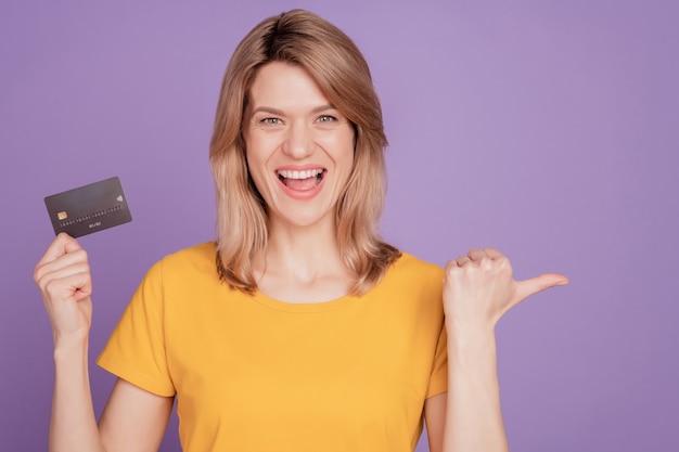 若い魅力的な女性の写真幸せなポジティブ笑顔クレジットカードポイント親指空のスペース紫の色の背景で隔離