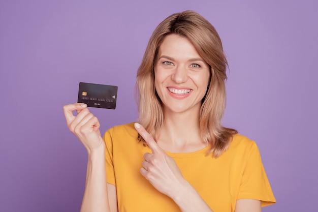 若い魅力的な女性の写真幸せなポジティブな笑顔ポイント指クレジットカード広告アドバイス紫の色の背景に分離