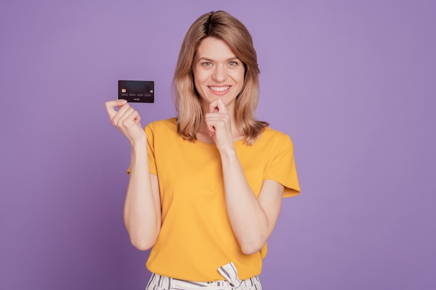 젊은 매력적인 여성의 행복한 긍정적인 미소의 사진은 보라색 배경에 격리된 신용카드 급여를 자신감 있게 들고 있다고 생각합니다.