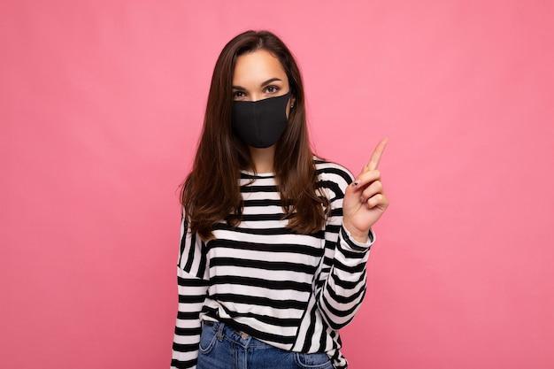 カラフルな背景の壁に分離された手作りの綿生地のフェイスマスクを身に着けている若い魅力的な女性の写真。 covid-19に対する保護。コピースペース