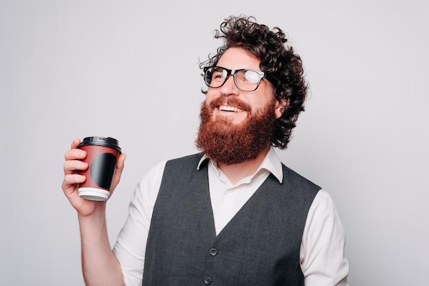 笑顔でコーヒーを飲みながらスーツを着た若いひげを生やしたヒップスターの男性の写真、リラックスする時間