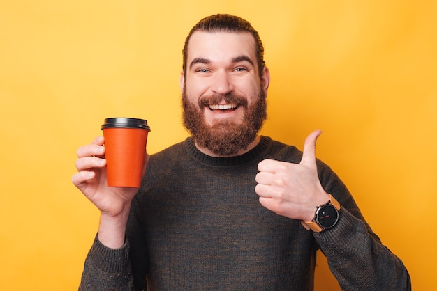 노란색 벽에 엄지 손가락을 보여주는 젊은 수염 된 hipster 남자의 사진