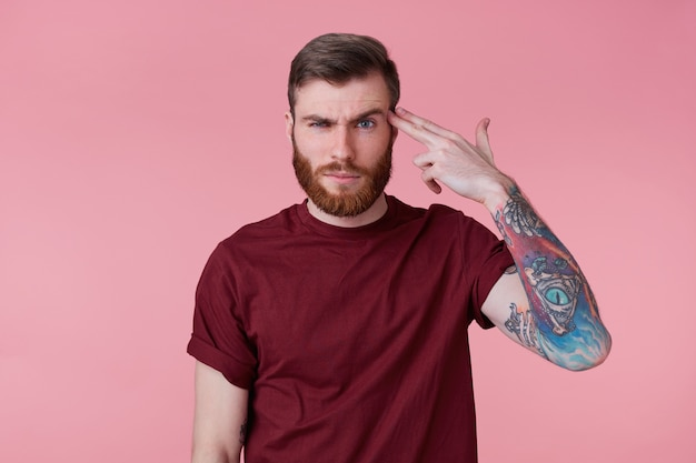 Фотография молодого бородатого мужчины с чернилами, изолированного на розовом фоне, стреляющего в его голову из ручного пистолета, показывая жест самоубийства.