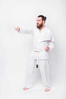 흰 벽 위에 태권도를 연습하는 도복 제복을 입은 젊은 수염 난 남자의 사진