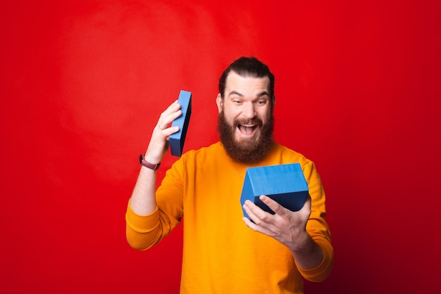 彼の贈り物に驚いている黄色のセーターを着た若いひげを生やした男の写真