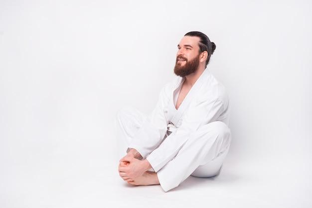 テコンドーの制服を着てストレッチ蝶のポーズをとる若いひげを生やした男の写真