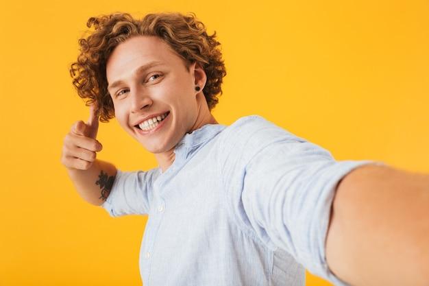 黄色の背景の上に分離された、自分撮り写真を撮り、カメラに指を指している若い美しい男の写真