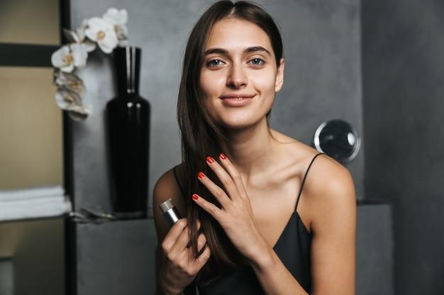 バスルームにいる若い美女の写真は、オイルで髪の毛をケアします。