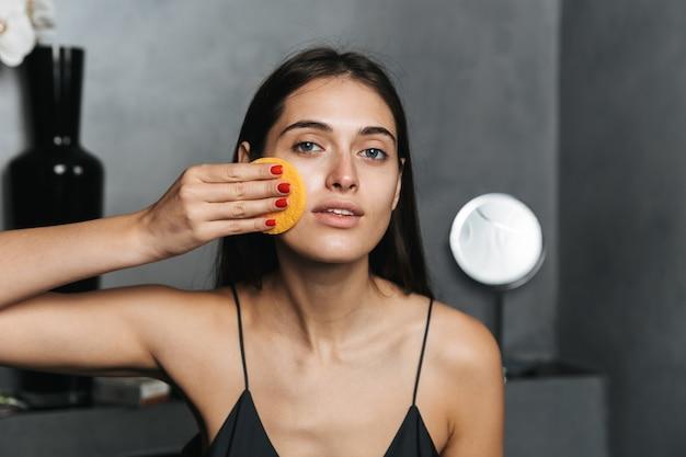 욕실에서 젊은 아름 다운 여자의 사진은 화장품으로 그녀의 피부를 돌봐 그녀의 얼굴을 청소합니다.