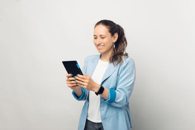白い壁にタブレットを使用して青いジャケットの若い美しい女性の写真