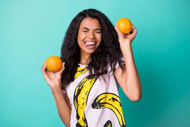 젊은 흑인 소녀의 사진은 두 개의 오렌지 혀를 들고 바나나 프린트 티셔츠를 입고 청록색 배경을 분리했습니다.