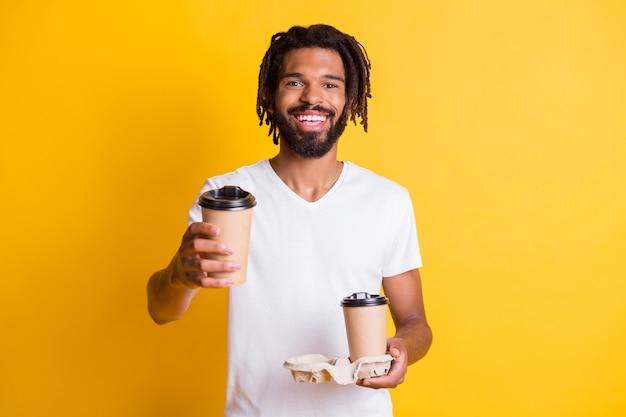 若い黒人男性の写真は、2杯のコーヒーを持ち帰りますあなたが飲むことを提案します白いtシャツを着て孤立した黄色の色の背景