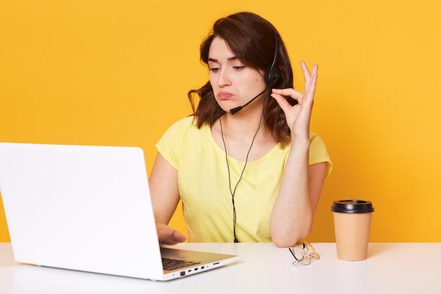 ビジネスセンターのアシスタント、若いブルネットの女性の写真は、ビデオ通話、ヘッドセットで座っている女性を介してクライアントに相談を与えます