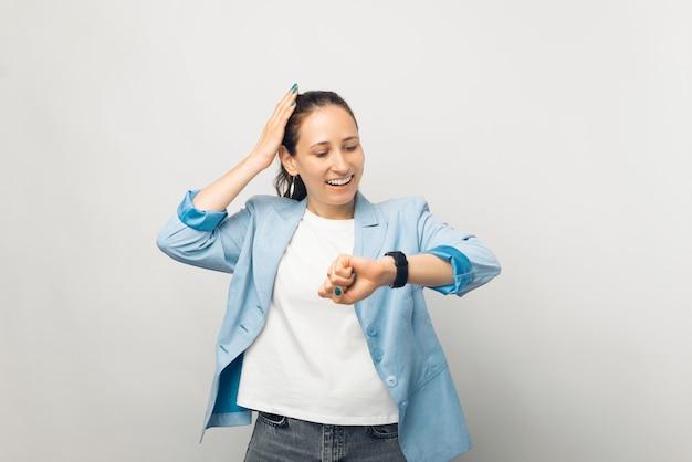 白い背景の上にカジュアルに立って、スマートウォッチに驚いて見ている若いビジネス女性の写真