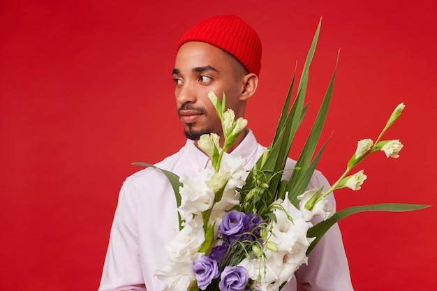 若い穏やかな暗い肌の男の写真は、白いシャツと赤い帽子を着て、目をそらし、花束を保持し、赤い背景の上に立っています。