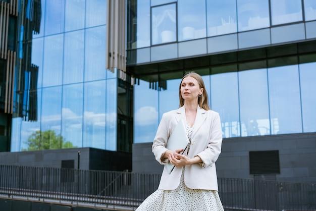 사무실 건물 배경에 서 있는 젊은 백인 쾌활한 비즈니스 여성의 사진...