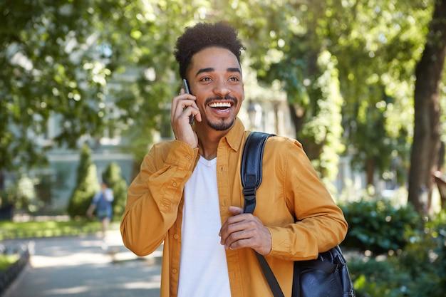黄色いシャツを着た陽気なアフリカ系アメリカ人の少年の写真。公園を歩いて、スマートフォンで話し、友人を待って、目をそらし、広く笑っています。この晴れた日はとても幸せです!