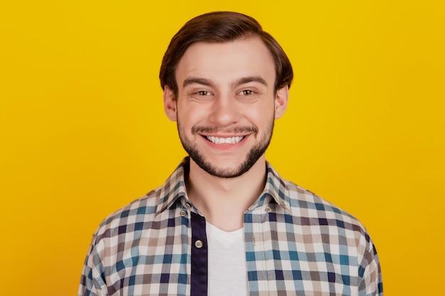 若い陽気な男の幸せなポジティブな笑顔の写真黄色の背景に分離された自信を持ってカジュアルな服装