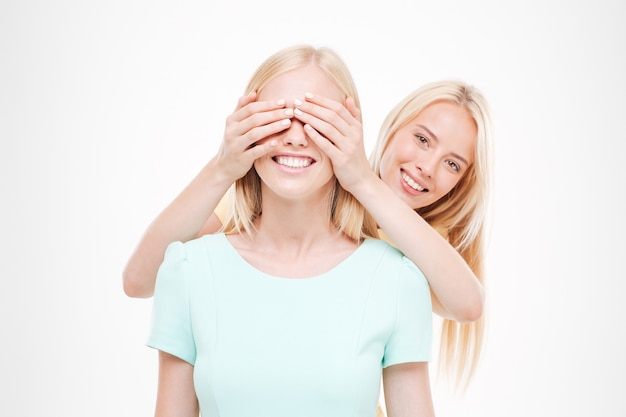 白い壁に隔離された彼女のfrienの目を覆っている若い陽気な女性の写真。