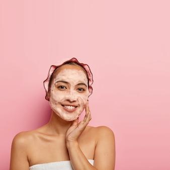 젊은 중국 여성의 사진은 정화 os 얼굴 피부를 즐기고, 비누로 씻고, 뺨에 닿으며, 미소로 보이며, 모공을 청소하고, 목욕 모자를 쓰고, 실내 포즈를 취하고, 분홍색 벽에 공간을 복사합니다.