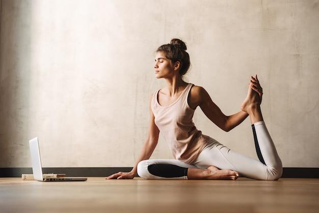 Фото молодой сосредоточенной женщины в спортивной одежде, делающей упражнения йоги с ноутбуком, сидя на полу дома