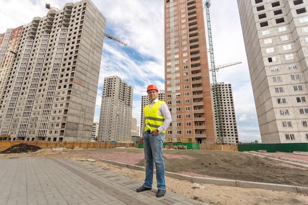 건설중인 건물 앞에 서있는 젊은 건설 엔지니어의 사진