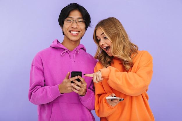 Фотография молодых студентов друзей пары стоя изолированно, используя мобильные телефоны.