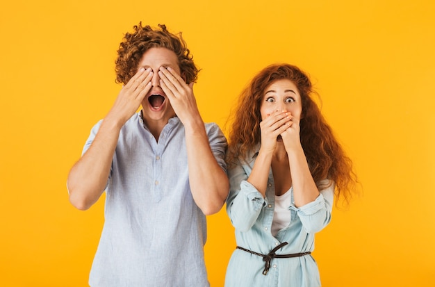黄色の背景で隔離、目と口を覆う基本的な服を着た若いカップルの男性と女性の写真