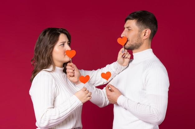 Фото молодой пары, красный фон. закрывают рты бумажными сердечками ручной работы
