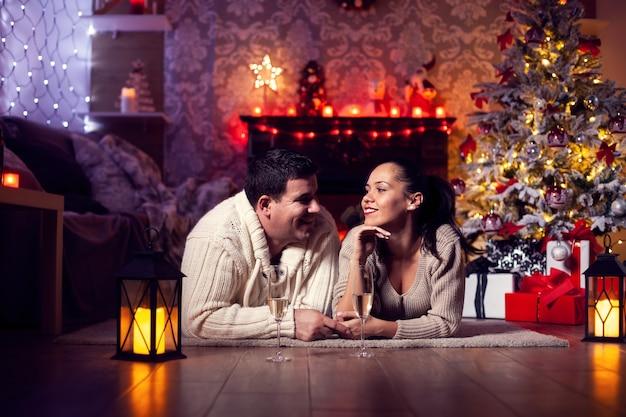 クリスマスの部屋でfireplaecのそばで休んでいる若いカップルの写真。クリスマスを祝う。クリスマスツリー。