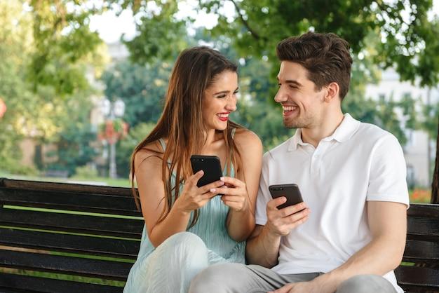 携帯電話を使用しながら屋外に座っている若いかわいい愛情のあるカップルの写真