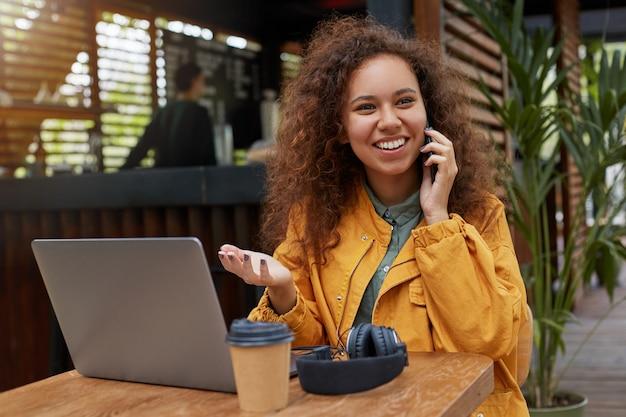 Фотография молодой темнокожей кудрявой женщины, сидящей на террасе кафе, в желтом пальто, работает за ноутбуком, пьет кофе, улыбается и разговаривает по телефону с другом.