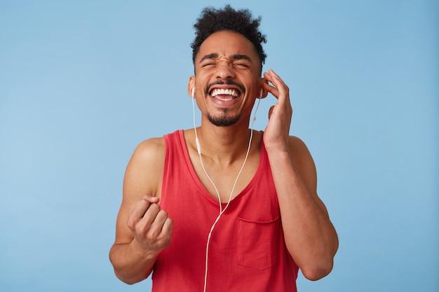 젊은 어두운 피부를 가진 남자의 사진은 위대하고 매우 행복하며 눈을 감고 주먹을 움켜 쥐고 좋아하는 노래를 즐기고 스탠드를 따라 노래합니다.