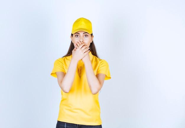 白い壁に口を抱えている若い配達員の写真。