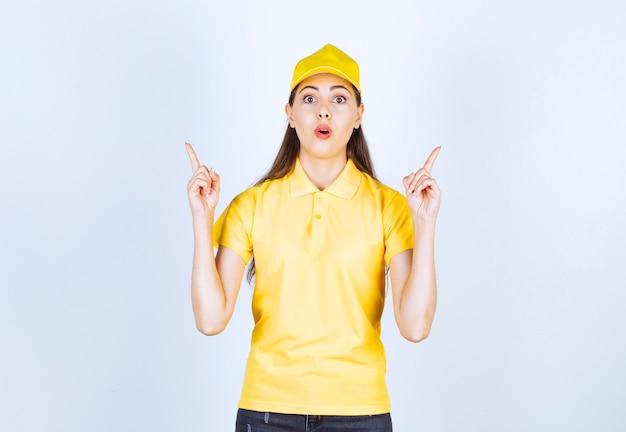 Фотография молодой доставляющей покупки на дом, указывая куда-то над белой стеной.
