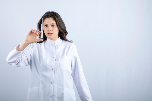 灰色の上に注射器が立っている若い医者の写真。