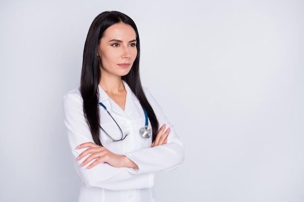 Фотография молодой женщины-врача в белом лабораторном халате, скрестив руки, смотрят в пустое пространство на сером фоне