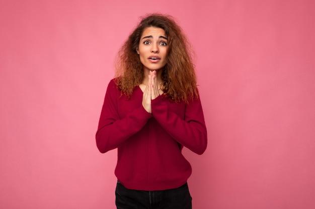 트렌디한 핑크색 옷을 입은 진지한 감정을 가진 젊은 감성적인 아름다운 갈색 곱슬머리 여성의 사진
