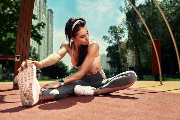 Фото молодой европейской женщины на уличной тренировке в спортивном парке в солнечный день концепция обучения на открытом воздухе.