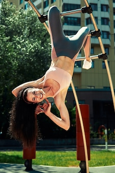 晴れた日にスポーツ公園でストリートワークアウトの若いヨーロッパの女性の写真
