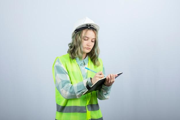 白い壁の上のノートに彼女のアイデアを書いている若い女性エンジニアの写真。高品質の写真