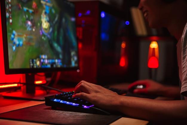Фотография молодого геймера, смотрящего на экран и играющего в видеоигры на компьютере в темной комнате, в наушниках и использующего радужную клавиатуру с подсветкой