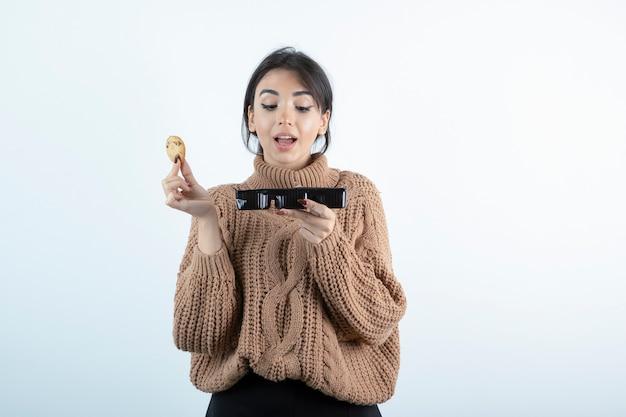 흰색 바탕에 칩 쿠키를 먹는 젊은 여자의 사진.