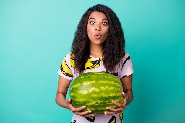 Фотография молодой девушки, держащей тяжелый арбуз, шокировано выражением лица, носит футболку с банановым принтом, изолированный бирюзовый цвет фона