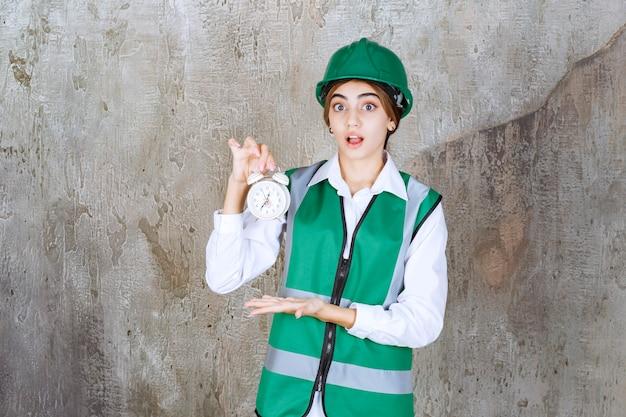 緑のベストと目覚まし時計を保持しているヘルメットの少女の写真