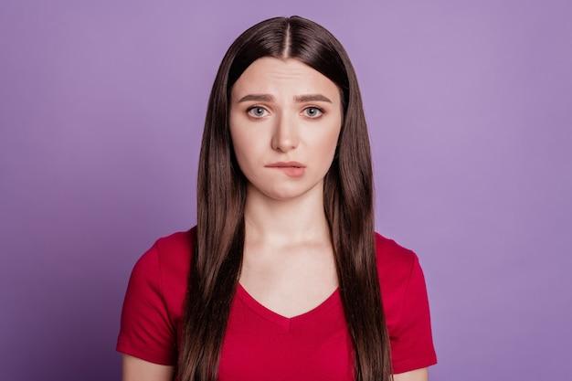 Фотография молодой девушки несчастной расстроенной обеспокоенной нервной укусом губ, зубов, изолированных на фиолетовом цветном фоне
