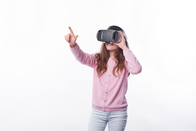 Фотография молодой девушки в очках vr, указывающей на что-то